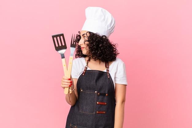 Ładna arabska kobieta myśląca, wyobrażająca sobie lub marząca o widoku profilu. koncepcja szefa kuchni grilla