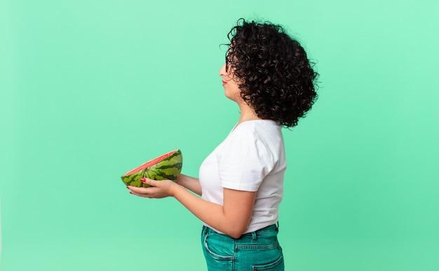 Ładna arabska kobieta o widoku profilu myśląca, wyobrażająca sobie lub marząca i trzymająca arbuza. koncepcja lato