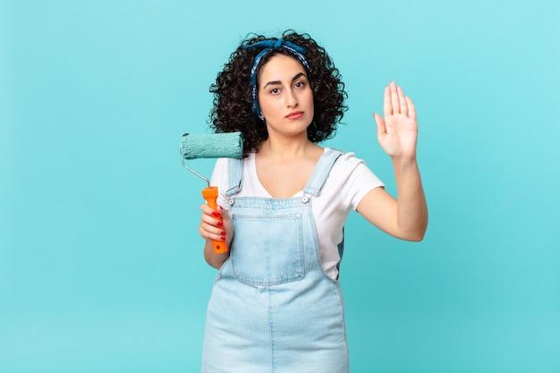 Ładna arabska kobieta szuka poważnego pokazując otwartą dłoń co gest stop. koncepcja malowania domu