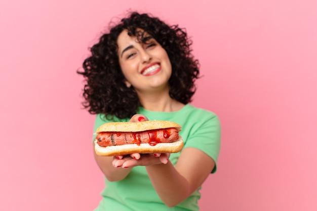 Ładna arabska kobieta trzyma hot doga. koncepcja fast food