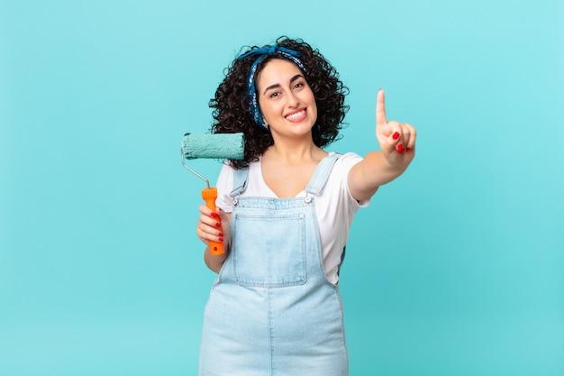 Ładna arabska kobieta uśmiecha się i wygląda przyjaźnie, pokazując numer jeden. koncepcja malowania domu