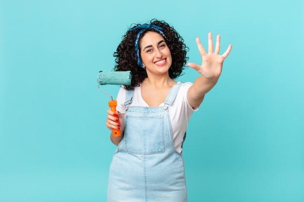 Ładna arabska kobieta uśmiecha się i wygląda przyjaźnie, pokazując numer pięć. koncepcja malowania domu