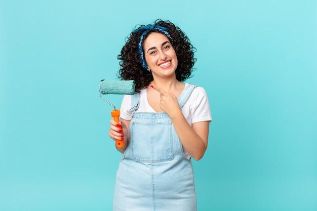 Ładna arabska kobieta uśmiecha się radośnie, czuje się szczęśliwa i wskazuje na bok. koncepcja malowania domu
