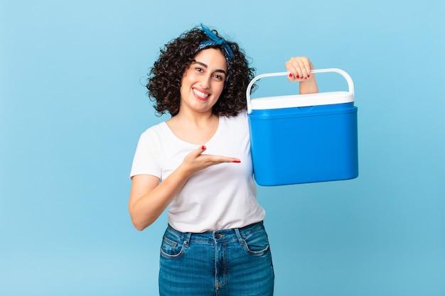 Ładna arabska kobieta uśmiecha się radośnie, czuje się szczęśliwa, pokazuje koncepcję i trzyma przenośną lodówkę