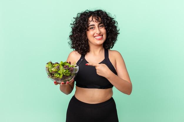 Ładna arabska kobieta uśmiecha się radośnie, czuje się szczęśliwa, wskazuje na bok i trzyma sałatkę. koncepcja diety