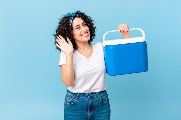 Ładna arabska kobieta uśmiecha się radośnie, macha ręką, wita cię i wita i trzyma przenośną lodówkę