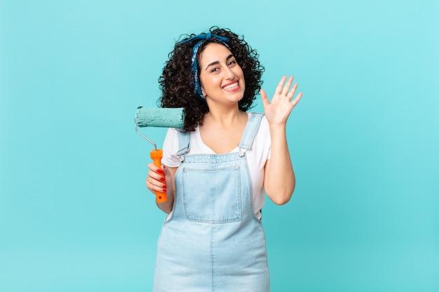 Ładna arabska kobieta uśmiecha się radośnie, machając ręką, witając cię i pozdrawiając. koncepcja malowania domu