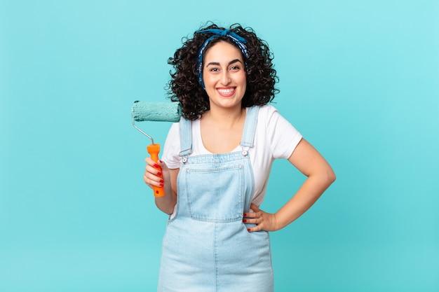 Ładna arabska kobieta uśmiecha się radośnie z ręką na biodrze i pewnie. koncepcja malowania domu