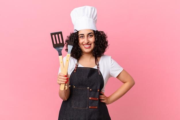 Ładna arabska kobieta uśmiecha się radośnie z ręką na biodrze i pewnie. koncepcja szefa kuchni grilla