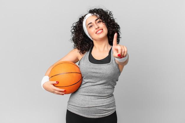 Ładna arabska kobieta uśmiechając się dumnie i pewnie robiąc numer jeden i trzymając piłkę do koszykówki. koncepcja sportu