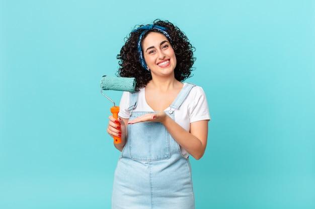 Ładna arabska kobieta uśmiechając się radośnie, czując się szczęśliwa i pokazując koncepcję. koncepcja malowania domu