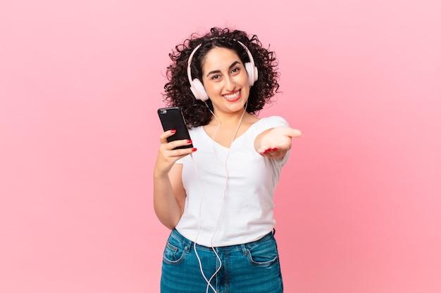 Ładna arabska kobieta uśmiechająca się radośnie, oferująca i pokazująca koncepcję ze słuchawkami i smartfonem