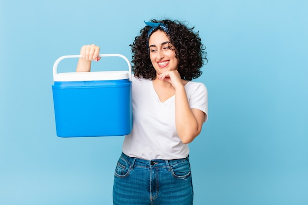 Ładna arabska kobieta uśmiechająca się ze szczęśliwym, pewnym siebie wyrazem twarzy z ręką na brodzie i trzymająca przenośną lodówkę