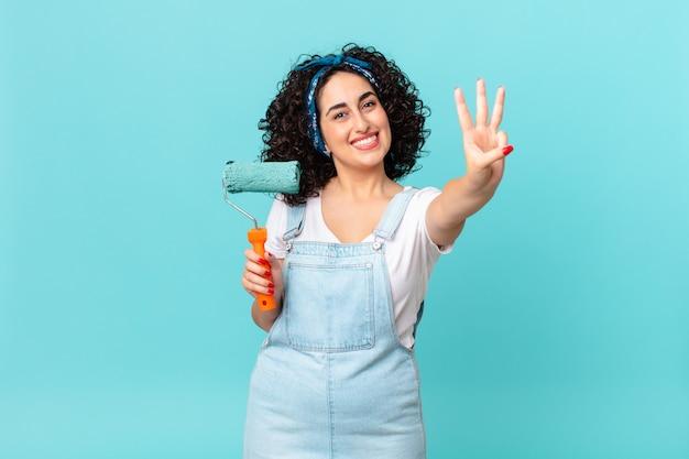 Ładna arabska kobieta uśmiechnięta i przyjazna, pokazująca numer trzy. koncepcja malowania domu