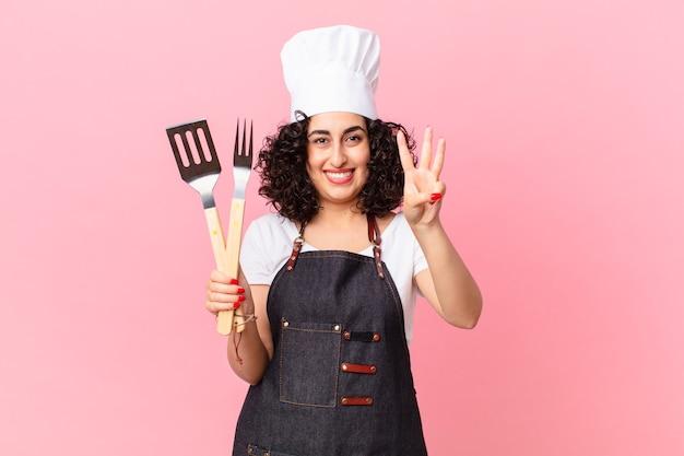 Ładna arabska kobieta uśmiechnięta i przyjazna, pokazująca numer trzy. koncepcja szefa kuchni grilla