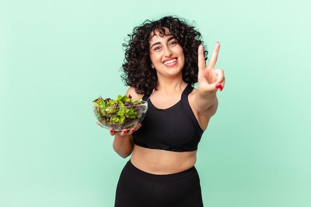 Ładna arabska kobieta uśmiechnięta i wyglądająca na szczęśliwą, gestykulująca zwycięstwo lub pokój i trzymająca sałatkę. koncepcja diety