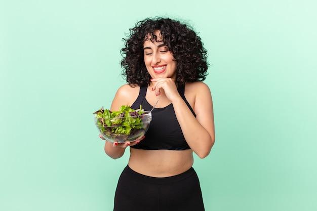Ładna arabska kobieta uśmiechnięta ze szczęśliwym, pewnym siebie wyrazem twarzy z ręką na brodzie i trzymająca sałatkę. koncepcja diety