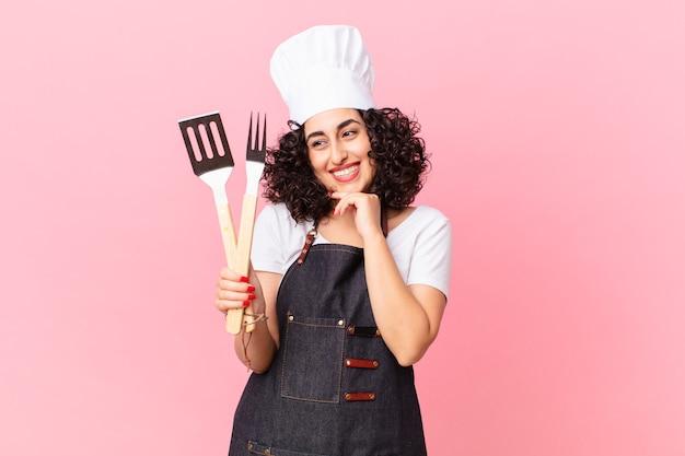 Ładna arabska kobieta uśmiechnięta ze szczęśliwym, pewnym siebie wyrazem twarzy z ręką na brodzie. koncepcja szefa kuchni grilla