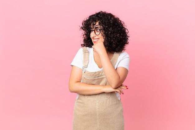 Ładna arabska kobieta uśmiechnięta ze szczęśliwym, pewnym siebie wyrazem twarzy z ręką na brodzie