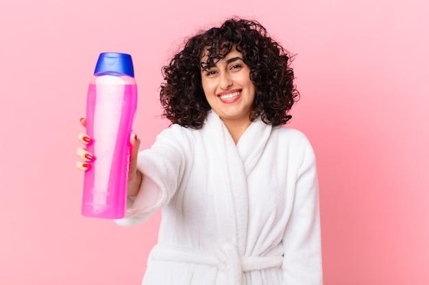 Ładna arabska kobieta w szlafroku i trzymająca butelkę szamponu