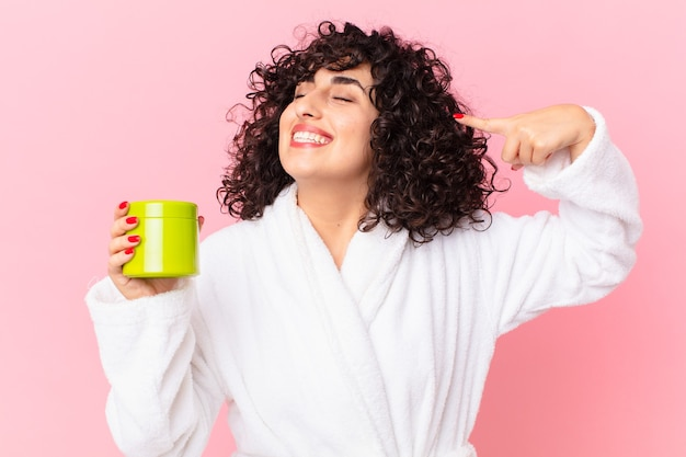 Ładna arabska kobieta w szlafroku i trzymająca odżywkę