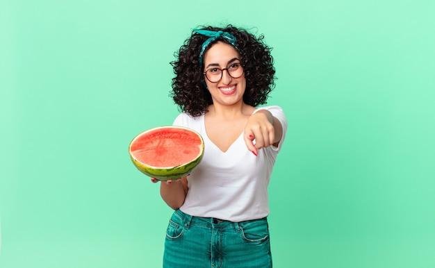 Ładna arabska kobieta, wskazując na aparat, wybierając ciebie i trzymając arbuza. koncepcja lato
