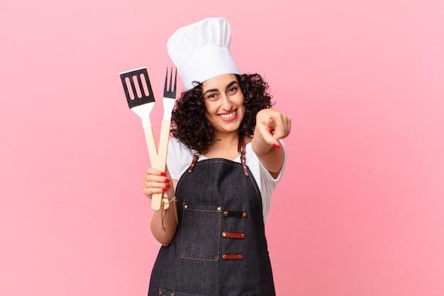 Ładna arabska kobieta, wskazując na aparat wybierając ciebie. koncepcja szefa kuchni grilla