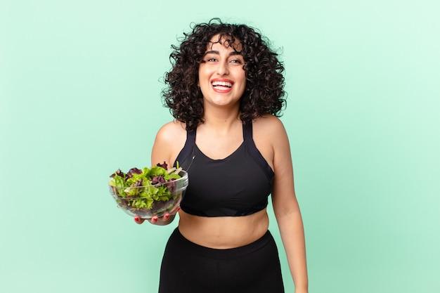 Ładna arabska kobieta wygląda na szczęśliwą i mile zaskoczoną i trzyma sałatkę. koncepcja diety