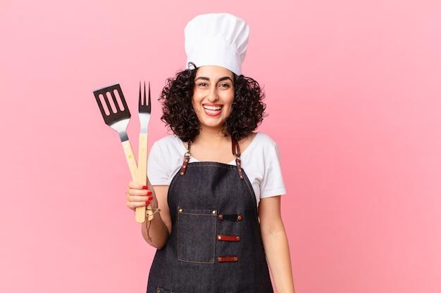 Ładna arabska kobieta wygląda na szczęśliwą i mile zaskoczoną. koncepcja szefa kuchni grilla