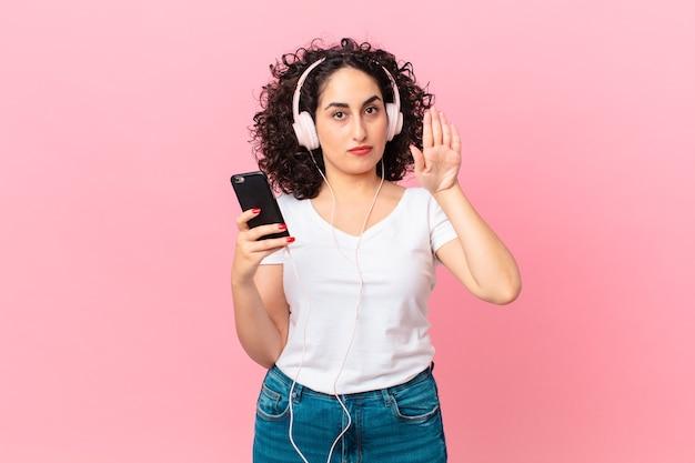 Ładna arabska kobieta wygląda poważnie pokazując otwartą dłoń, wykonując gest zatrzymania ze słuchawkami i smartfonem