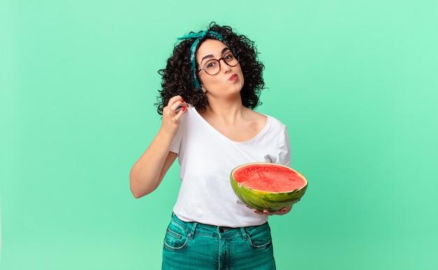 Ładna arabska kobieta wyglądająca arogancko, odnosząca sukcesy, pozytywna i dumna, trzymająca arbuza. koncepcja lato
