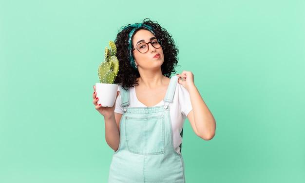 Ładna arabska kobieta wyglądająca arogancko, odnosząca sukcesy, pozytywna i dumna, trzymająca doniczkowego kaktusa