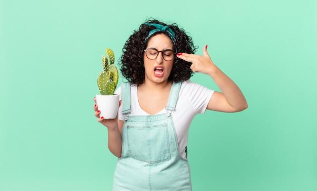 Ładna arabska kobieta wyglądająca na nieszczęśliwą i zestresowaną, samobójczy gest wykonujący znak pistoletu i trzymający kaktusa w doniczce