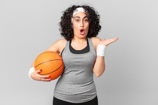 Ładna arabska kobieta wyglądająca na zaskoczoną i zszokowaną, z opuszczoną szczęką, trzymająca przedmiot i trzymającą piłkę do koszykówki. koncepcja sportu