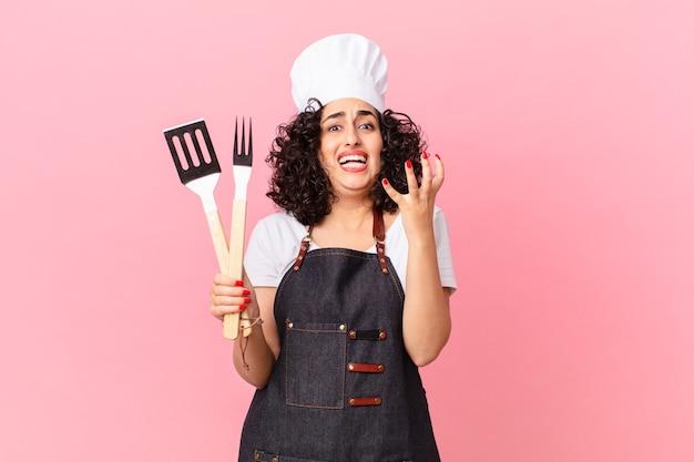 Ładna arabska kobieta wyglądająca na zdesperowaną, sfrustrowaną i zestresowaną. koncepcja szefa kuchni grilla
