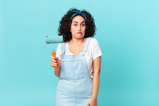 Ładna arabska kobieta wyglądająca na zdziwioną i zdezorientowaną. koncepcja malowania domu