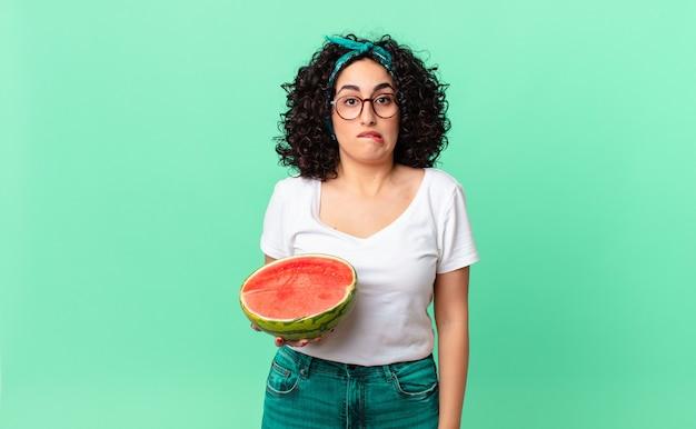 Ładna arabska kobieta wyglądająca na zdziwioną i zdezorientowaną, trzymająca arbuza. koncepcja lato