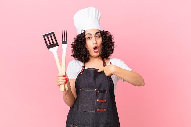 Ładna arabska kobieta wyglądająca na zszokowaną i zaskoczoną z szeroko otwartymi ustami, wskazując na siebie. koncepcja szefa kuchni grilla