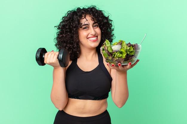 Ładna arabska kobieta z hantlami i sałatką. koncepcja fitness
