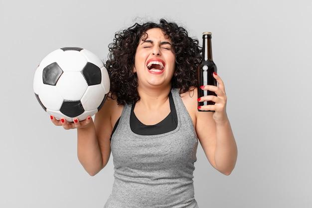 Ładna arabska kobieta z piłką nożną i pijącą piwo