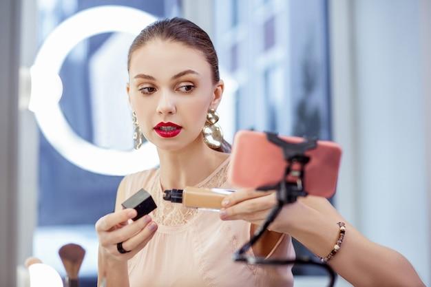 Ładna, atrakcyjna kobieta, która udziela porad na temat kosmetyków, prowadząc jednocześnie swojego bloga o urodzie