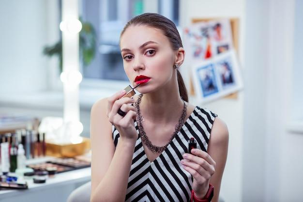 Ładna, atrakcyjna kobieta nakłada czerwoną szminkę podczas makijażu