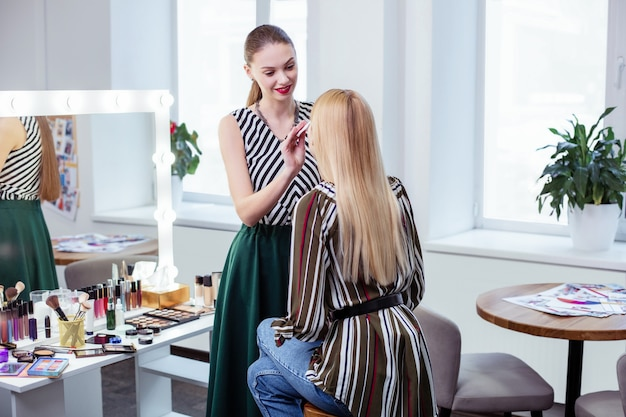 Ładna, atrakcyjna kobieta patrząca na swojego klienta podczas oczyszczania skóry