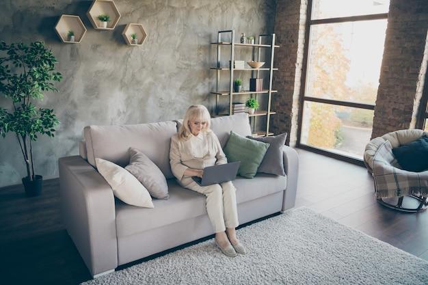 Ładna, atrakcyjna skoncentrowana, siwowłosa blond babcia w średnim wieku siedząca na sofie odpoczywająca za pomocą laptopa dzwoniącego do krewnych w industrialnym lofcie w nowoczesnym stylu wnętrza mieszkania mieszkanie