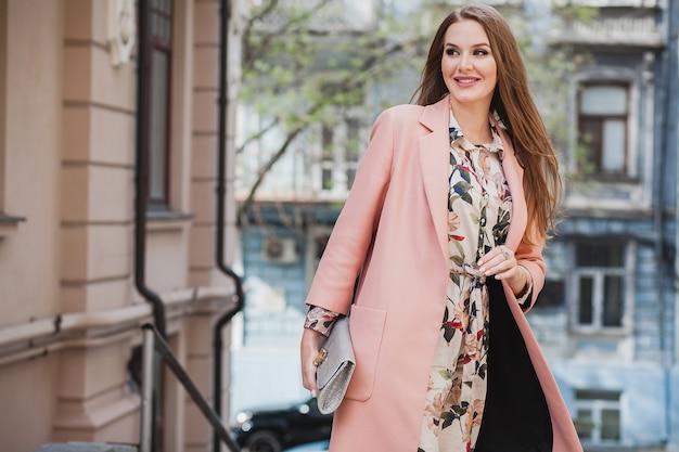 Ładna atrakcyjna stylowa uśmiechnięta kobieta spaceru ulicą miasta w różowy płaszcz wiosna trend w modzie trzymając torebkę
