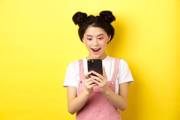 Ładna azjatycka dziewczyna patrząc podekscytowana na ekranie, czytająca wiadomość na telefonie i uśmiechnięta szczęśliwa, stojąca w letnich ubraniach na żółtym tle