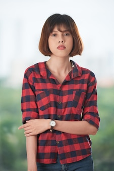 Ładna azjatycka dziewczyna patrzeje kamerę jest ubranym szkockiej kraty koszula