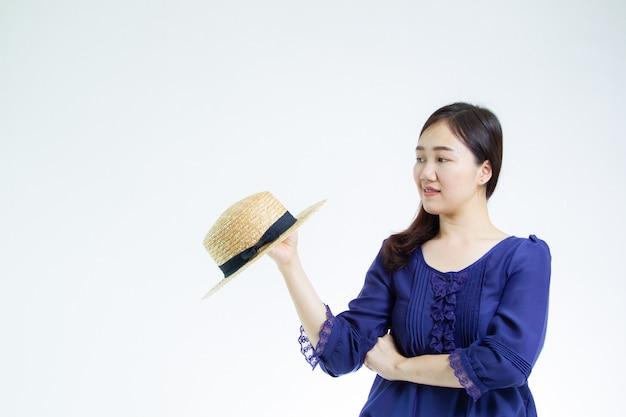 Ładna azjatycka kobieta jest ubranym kapeluszowego portreta zakończenie up na bielu z copyspace.