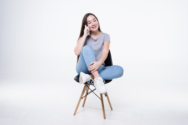 Ładna azjatycka kobieta rozmawia przez inteligentny telefon na białym tle na białej ścianie