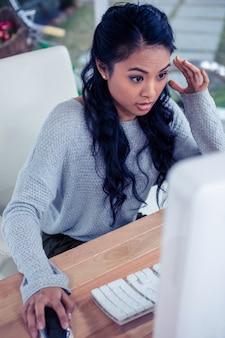 Ładna azjatycka kobieta używa komputer w biurze